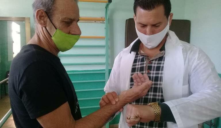 Especialista Marciel Pérez Hernández, de la Sala de Rehabilitación Integral de Jaruco, a Juan Carlos Arián de la Nuez, en su primer día de terapia el dos de diciembre de 2020. Foto Marlene Caboverde